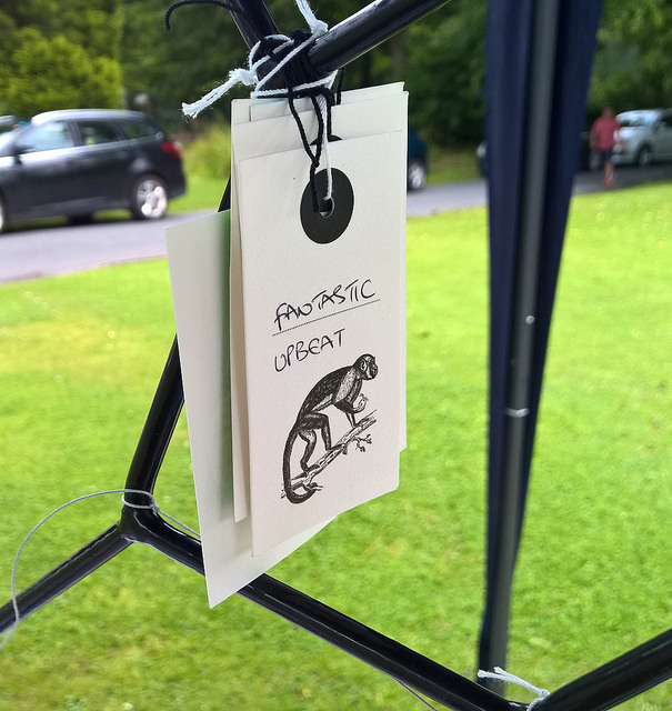 Photo of a paper tag hanging from a small metal tree. The tag shows a Victorian illustration of a monkey. Under the monkey someone has written two words to describe the museum, which say fantastic and upbeat.