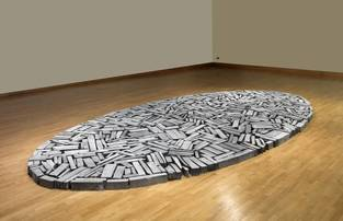 Photo of large room with wooden floor and white walls. In the middle of the space is a large flat oval shaped arrangement of slices of pale grey slate. This is an artwork by Richard Long.